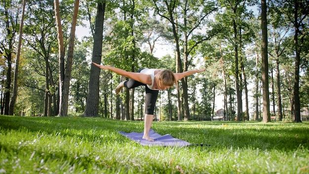 스트레칭과 요가 운동을 하는 피트니스 옷을 입고 웃고 있는 중년 여성의 이미지. 공원 잔디에 있는 피트니스 매트에서 명상을 하고 스포츠를 하는 여성