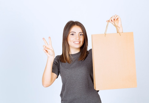 종이 가방을 들고 승리 기호를 보여주는 웃는 여자의 이미지.