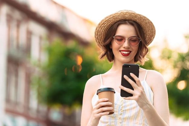 Изображение улыбающейся женщины в платье, соломенной шляпе и солнцезащитных очках, использующей смартфон на открытом воздухе