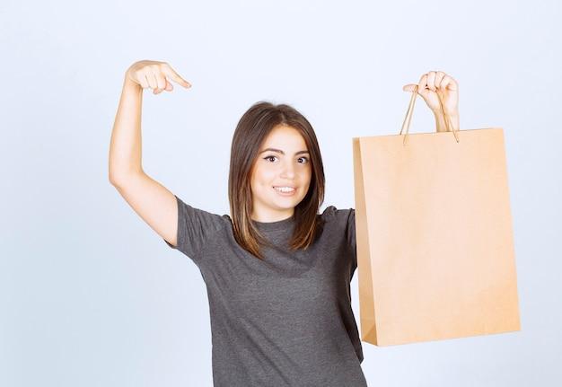 종이 가방을 가리키고 포즈 웃는 여자의 이미지.