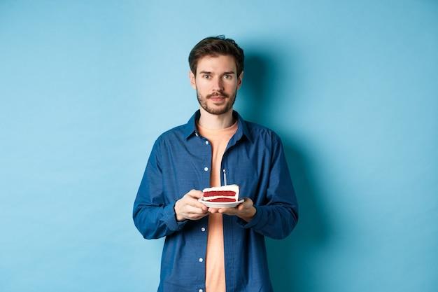 생일을 축 하 하 고 조명 된 촛불 b-day 케이크를 들고 파란색 배경 위에 서있는 카메라를보고 웃는 젊은 남자의 이미지.