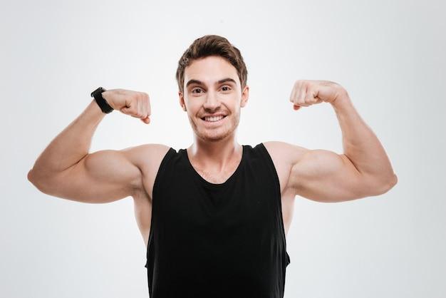 Изображение улыбающегося молодого человека, одетого в черную футболку, стоящего над белой стеной, показывая его бицепсы.
