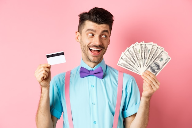 プラスチック製のクレジットカードを保持し、お金を幸せそうに見て、現金を選択し、ピンクの背景の上に立って蝶ネクタイで若い男の笑顔の画像。