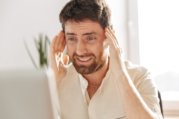 Изображение подчеркнутого офисного работника 30-х годов в белой рубашке, использующего ноутбук, сидя за столом на современном рабочем месте
