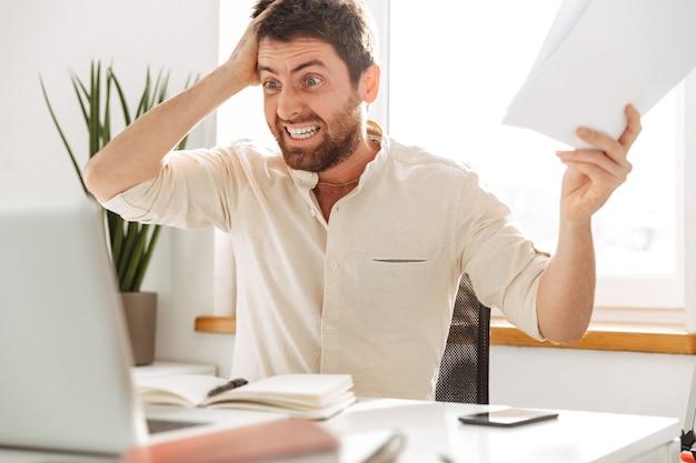 Изображение стрессового офисного работника 30-х годов в белой рубашке, использующего ноутбук и бумажные документы на современном рабочем месте