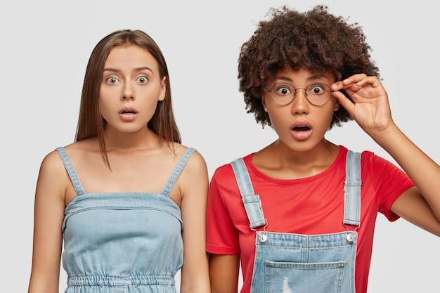 Изображение ошеломленной девушки смешанной расы смотрят в камеру с ошибочными глазами