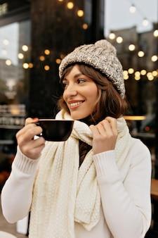 ニット帽とスカーフでコーヒーを飲み、冬の外で時間を楽しんでいるヨーロッパの女性のスタイリングの画像
