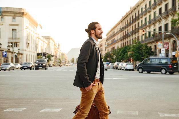 Изображение стильного бизнесмена в официальной одежде, пересекающего проспект в центре города с кожаной мужской сумкой в руке Premium Фотографии