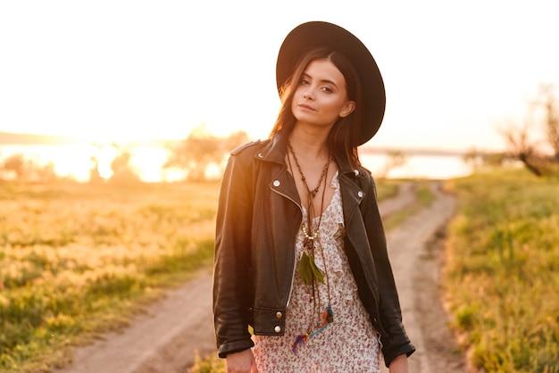 晴れた暖かい日中に田舎を歩きながらあなたを見ている革のジャケットと帽子を身に着けている長い髪を持つスタイリッシュなヨーロッパの女性のイメージ