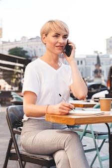 夏のカフェ屋外に座って、ノートに書き留めて携帯電話で話す基本的な服を着ているスタイリッシュな成熟した女性の画像