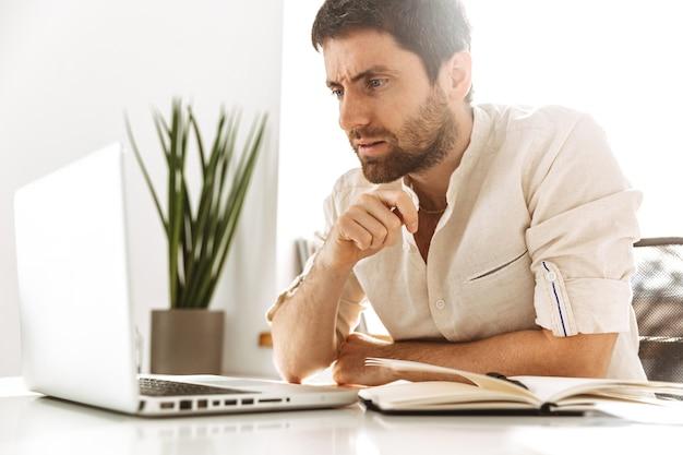 Изображение успешного делового мужчины 30-х годов в белой рубашке, работающего с ноутбуком и бумажными документами, сидя в ярком офисе