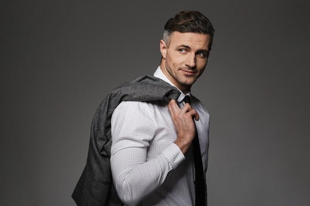 笑顔で衣装を着て、灰色の壁に分離された彼の肩にジャケットを保持している成功した実業家のイメージ