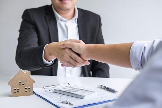 부동산의 성공적인 거래, 중개인 및 고객이 계약 승인 신청서에 서명한 후 악수하는 이미지, 주택 담보 대출 제안 및 주택 보험에 관한 것입니다.