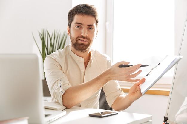Изображение успешного офисного парня 30-х годов в белой рубашке с ноутбуком и бумажными документами во время работы на современном рабочем месте
