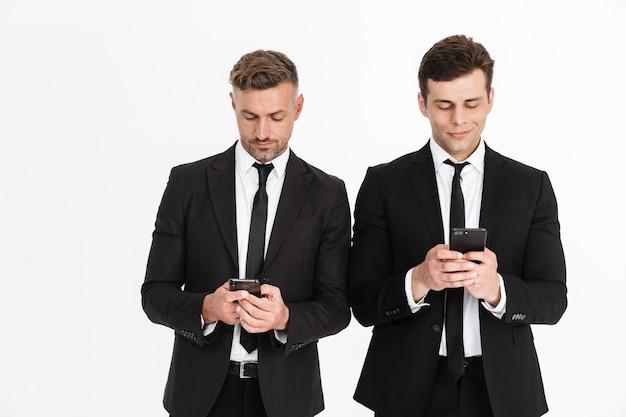 Изображение успешных серьезных двух бизнесменов в офисных костюмах, держащихся и печатающих на мобильных телефонах, изолированные