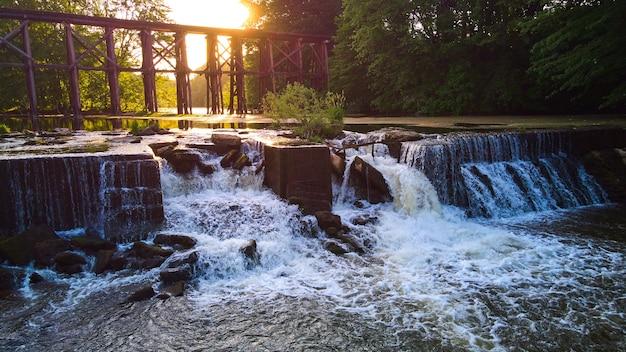人工ダムと滝のある水上鉄道の背後にある夕日の画像