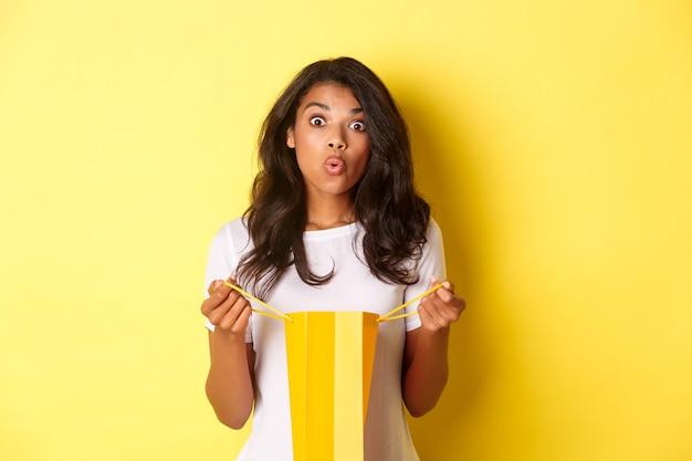 Изображение удивленной афро-американской девушки получают подарок на празднике, открывают сумку для покупок и выглядят изумленно, стоя на желтом фоне.