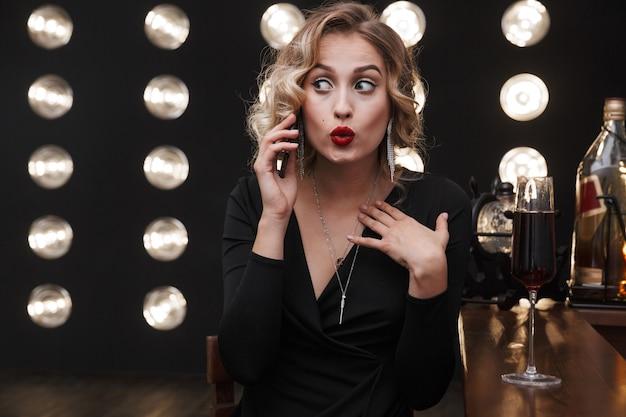 우아한 드레스를 입고 휴대폰으로 통화하고 바에서 레드 와인을 마시는 놀란 금발 여성의 이미지