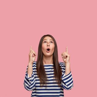 驚いた感情的な若い黒髪の10代の少女の画像は人差し指を上に上げます