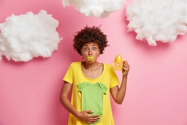 아늑한 집에서 놀란 미래의 어머니의 이미지, 배를 안고, 아기 바디 수트, 수유 병 및 임신 한 아내의 사진을 만드는 남편을위한 젖꼭지 포즈. 재미있는 기대 엄마