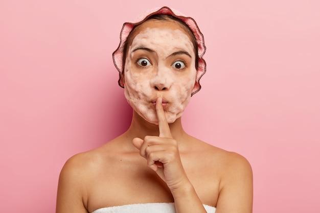 얼굴에 비누 방울을 얹은 놀란 한국 여성의 이미지, 침묵 제스처, 아름다움의 비밀을 말하고, 피부를 깨끗하게하고 각질을 제거하고, 자유 시간 동안 미용 시술을 받고, 자신을 돌 봅니다.