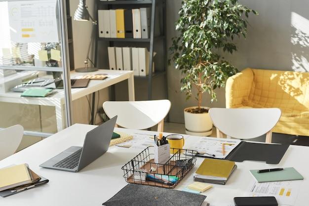Изображение стола с компьютером и документами и другими офисными принадлежностями в современном офисе