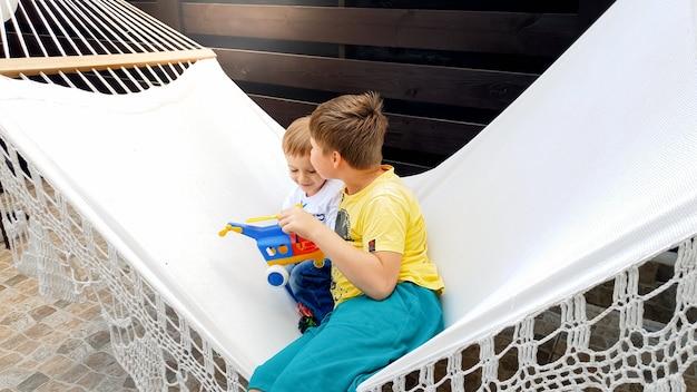 家の裏庭で彼の弟とハンモックに座ってスイングしている10代の少年の画像