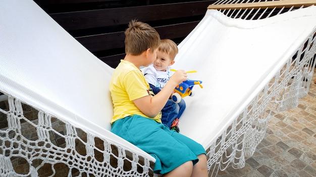 Изображение мальчика-подростка, сидящего и раскачивающегося в гамаке со своим младшим братом на заднем дворе дома