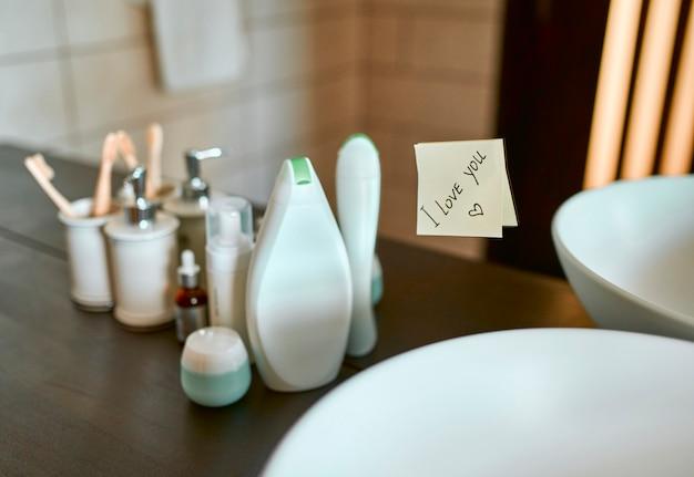 흰색 세면대, 메이크업 병, 칫솔이있는 욕실 이미지 비문이 적힌 거울 스티커에 나는 당신을 사랑합니다.