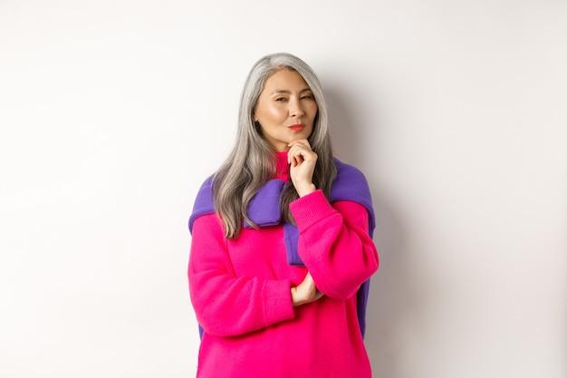 Изображение вдумчивой азиатской пожилой женщины, подозрительно косящейся на камеру, имеющей предположение, стоящей на белом фоне и думающей