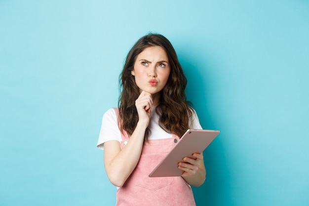 左上隅を見て考え、デジタルタブレットを持って、難しい選択をし、青い背景の上に立っている思いやりのある女子学生の画像。