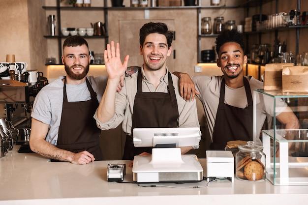 屋内で手を振っているカフェバーで働く3人の幸せなコーヒーの男性の同僚の画像。