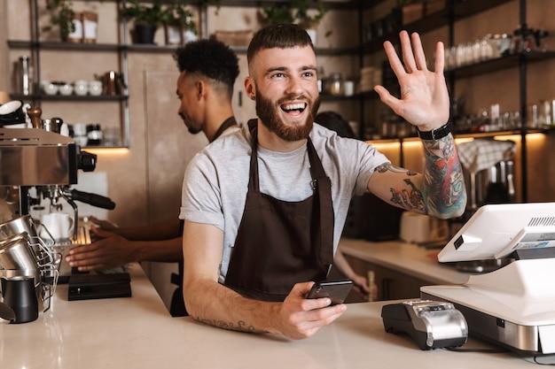 Изображение трех счастливых коллег мужчин кофе в кафе-баре, работающих в помещении, размахивая.