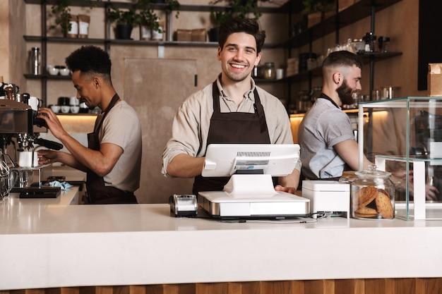 屋内で働いているカフェバーで3人の幸せなコーヒーの男性の同僚の画像。