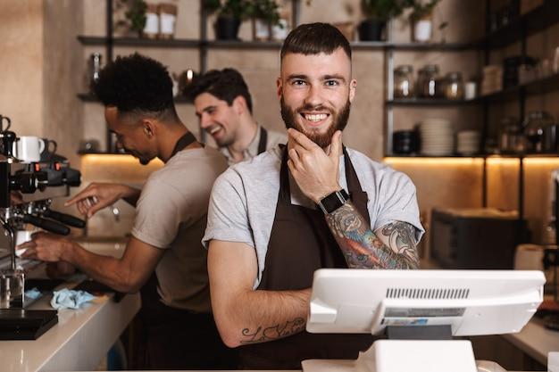 Изображение трех счастливых коллег мужчин кофе в кафе-баре, работающих в помещении.