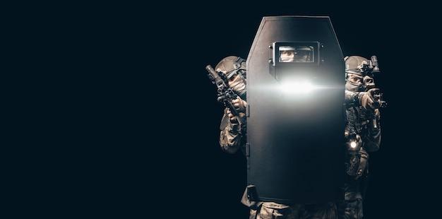 슈팅 컴퓨터 게임에서 세 군인의 이미지. e스포츠 개념입니다. 그들은 전술 방탄 방패 뒤에 숨어 있습니다. 혼합 매체