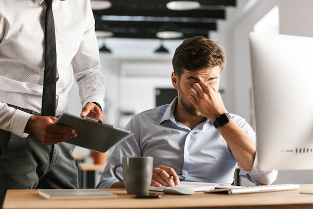 Изображение усталого делового человека, имеющего проблемы в работе, сидя за столом в офисе
