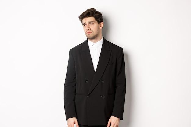 苦しめられた、暗い表情で左を見て、白い背景の上に疲れ果てて立っているコピースペースを左に見つめているスーツを着た疲れた男の画像。