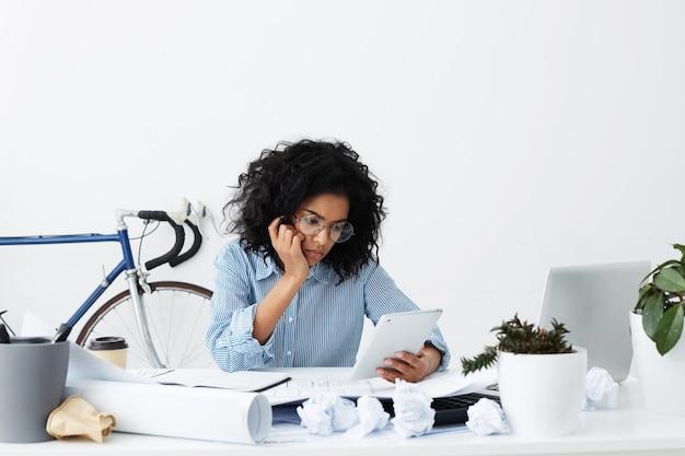 疲れている動揺して若いアフリカの女性のイメージはうんざりし、自宅で仕事をしながら眠そうです