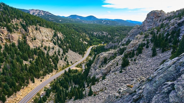 Изображение путешествующего автомобильного туризма через горы рядом с каменными пиками и соснами