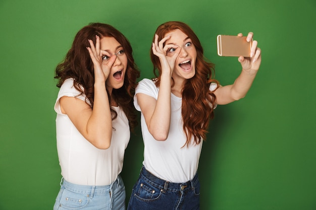 Изображение двух забавных девочек-подростков с рыжими волосами, делающих селфи на мобильном телефоне и показывающих знак ок возле глаз, изолированные на зеленом фоне