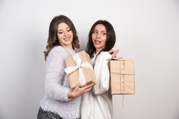 Изображение двух лучших друзей, стоящих вместе и держащих подарочные коробки.