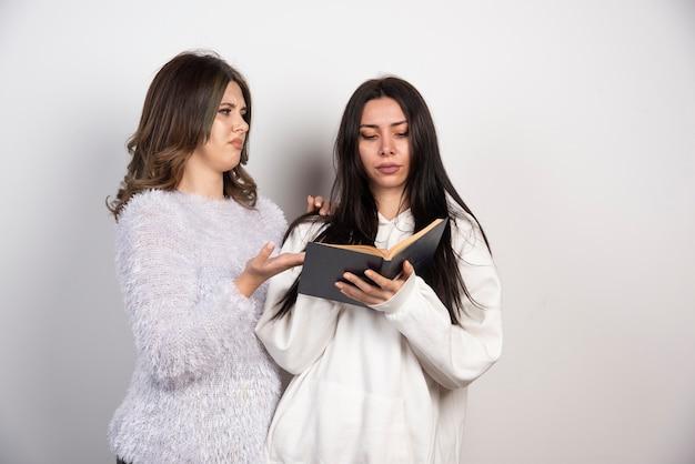 Изображение двух лучших друзей, стоящих вместе и смотрящих на книгу на белой стене.