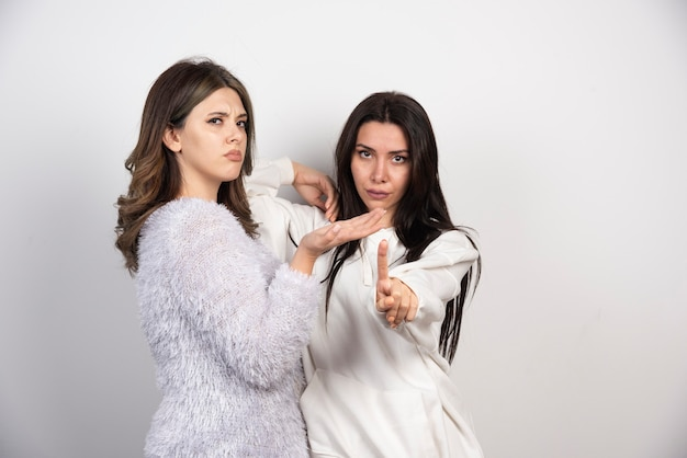 Изображение двух лучших друзей, стоящих вместе и смотрящих в камеру на белой стене.