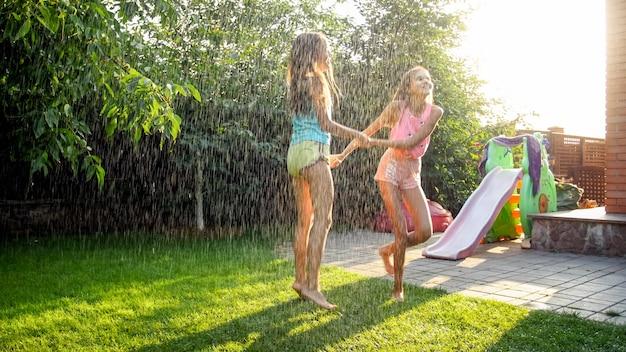 家の裏庭の庭で暖かい夏の雨の下でジャンプして踊っている2人の幸せな笑いの10代の少女の画像。夏に屋外で遊んで楽しんでいる家族