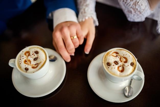 結婚指輪を持つ 2 人の手のイメージ。