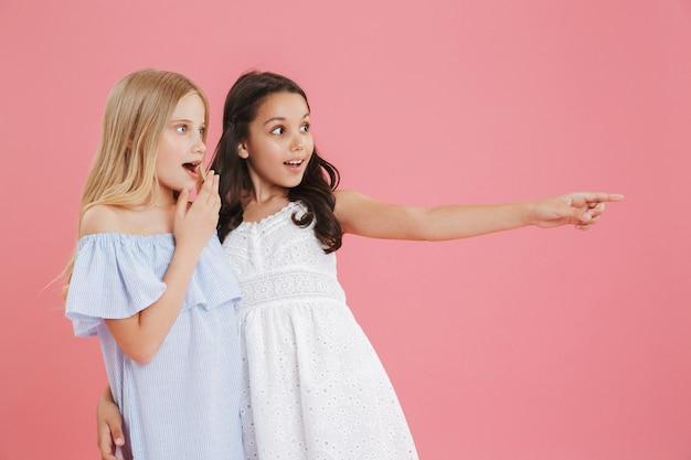Изображение двух удивленных и счастливых девочек 8-10 лет в платьях, смотрящих в сторону и указывающих пальцем на copyspace.