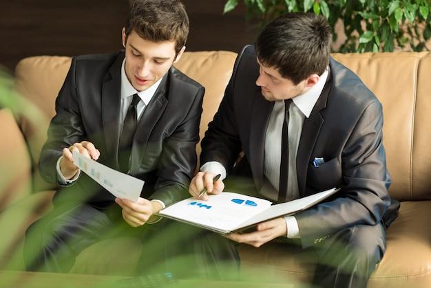 Изображение двух молодых бизнесменов, обсуждающих проект на встрече