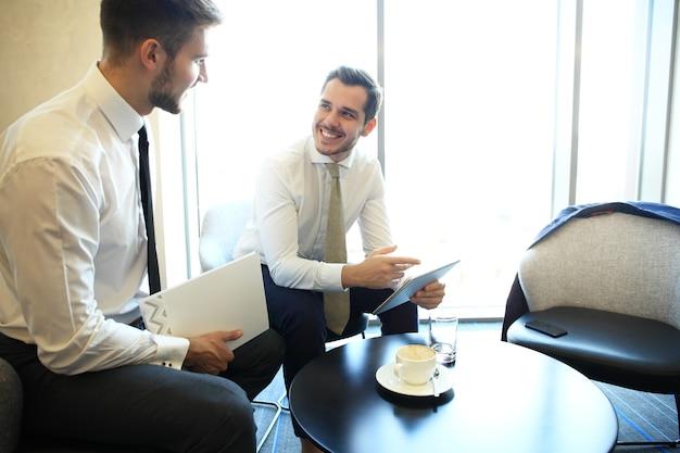 Изображение двух молодых бизнесменов, использующих тачпад на встрече.