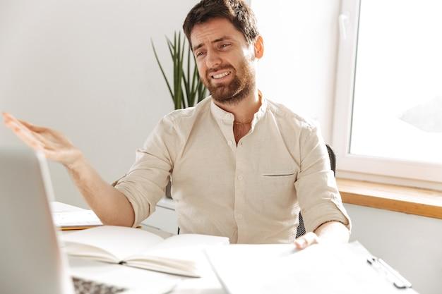 Изображение несчастного офисного работника 30-х годов в белой рубашке с ноутбуком и бумажными документами, сидящего за столом на современном рабочем месте